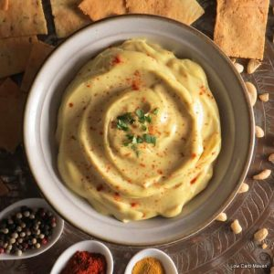 Creamy curry cashew cream dip in a bowl with crackers, cashew nuts and white spoons of vibrant spices.