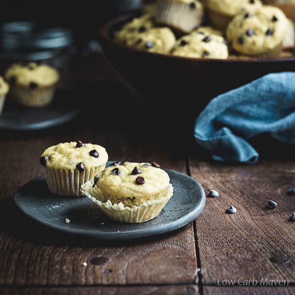 Mini chocolate chip muffins on a dark gray plate sitting on a wooden table with chocolate chips around the plate and large wooden bowl of muffins in the background with a blue napkin giving a pop of color to a decidedly brown photo.