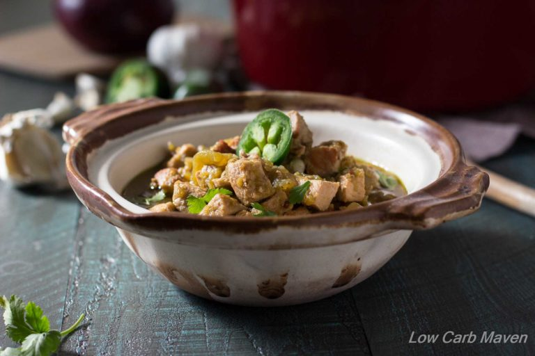 New Mexico Pork Chile Stew with Hatch chiles and topped in cilantro and a jalapeno in a rustic handled bowl on a turquoise wooden background with ingredients and a red Dutch oven in the background.