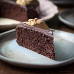 A slice of moist chocolate walnut cake with chocolate ganache and a walnut half served on a blue plate with the larger cake behind.