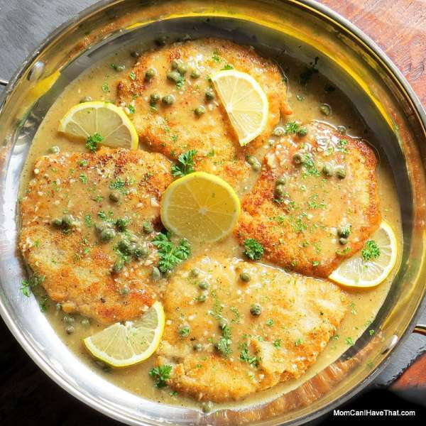 Top down view of 4 low carb breaded pork cutlets in a lemon butter caper sauce garnishes with lemon slices and parsley in a round stainless steel pan.