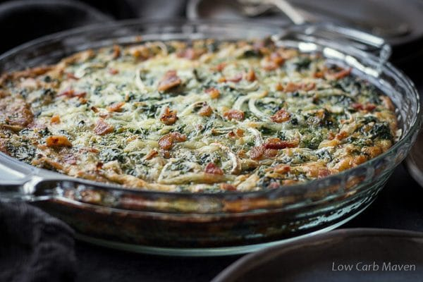 Crustless spinach and bacon quiche in a clear handled pie plate on a dark gray napkin.