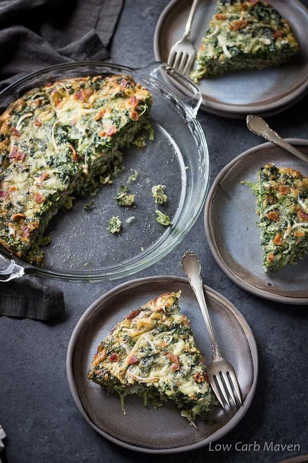 Low Carb Spinach and Bacon Crustless Quiche in a clear pie plate with slices on dark gray ceramic plates with silver spoons.