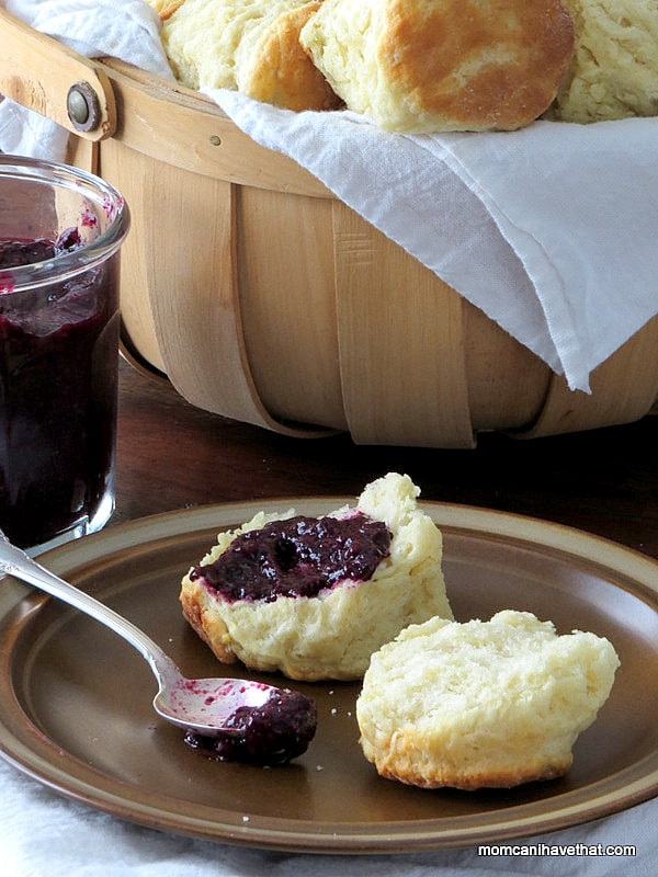 Southern buttermilk biscuits with jam on a plate with a basket of fluffy biscuits behind.