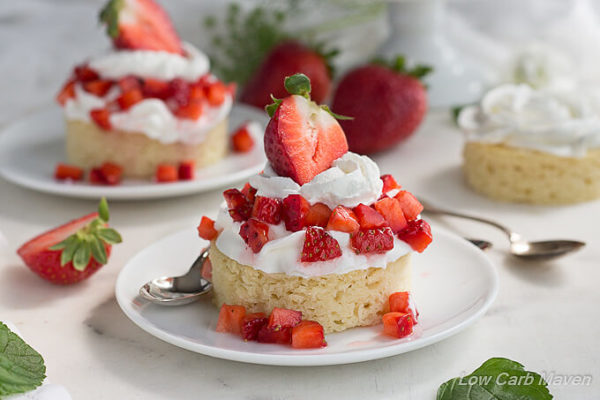 Moist almond flour cake on a round white plate, topped with whipped cream and diced fresh strawberries topped with more whipped cream and a large strawberry half with the leaves still attached. Another strawberry shortcake dessert is in the back ground along with fresh strawberries and mint leaves.