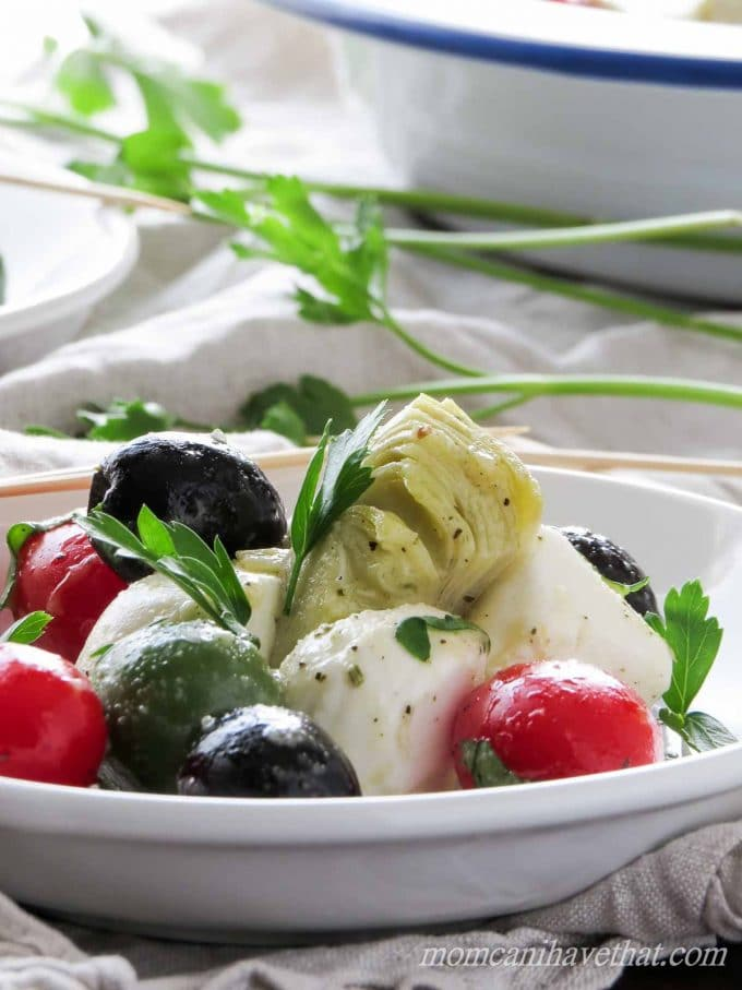 Caprese Salad with cherry tomatoes, olives and artichoke hearts in a white bowl on a napkin with parsley.
