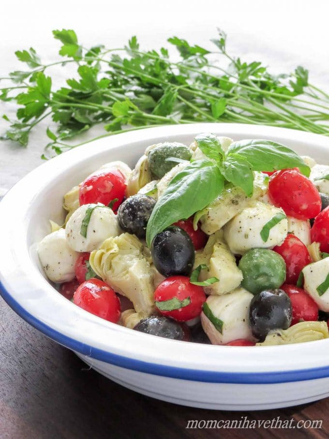 Caprese salad with cherry tomatoes, olives, and artichoke hearts garnished with basil in a white bowl with basil with parsley behind.