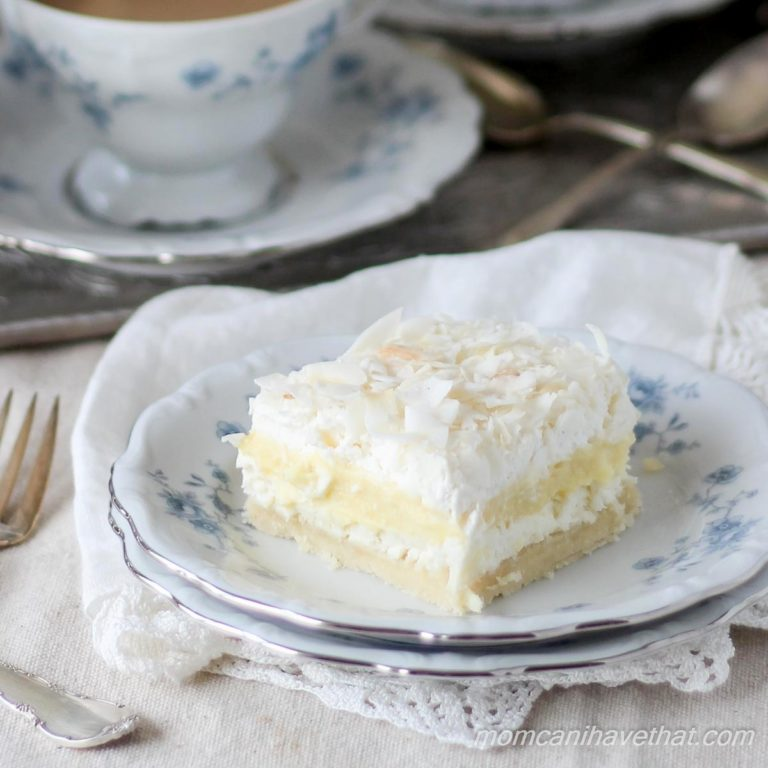 Coconut Cream Layered Dessert (Coconut Cream Delight), 5 layer dessert of a cookie base, cream cheese layer, coconut cream pudding layer, whipped cream and coconut flakes on a blue and white china plate with a lacy napkin beneath.