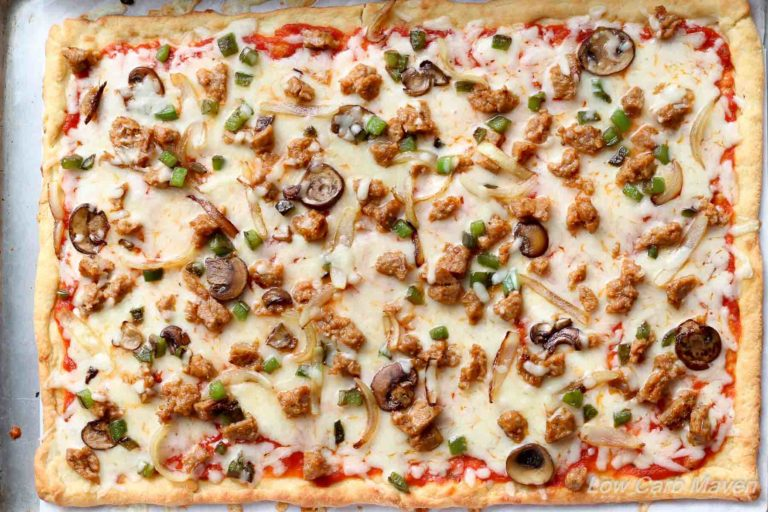 Birdseye view of low carb supreme pizza with fathead pizza crust and sauce, cheese, sausage, green bell pepper, onions and mushrooms on a sheet pan.