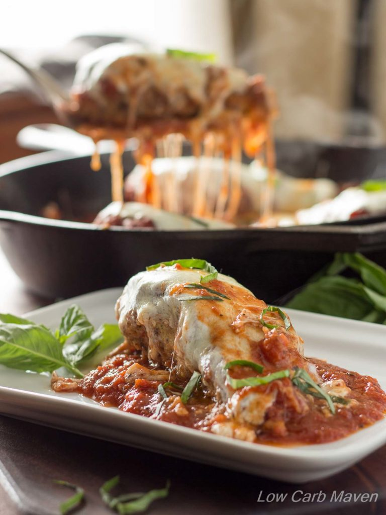 A serving of low carb chicken Parmesan on a plate with melty cheese and garnished with basil. A serving of chicken Parmesan is being lifted by a spatula from a skillet in the background.