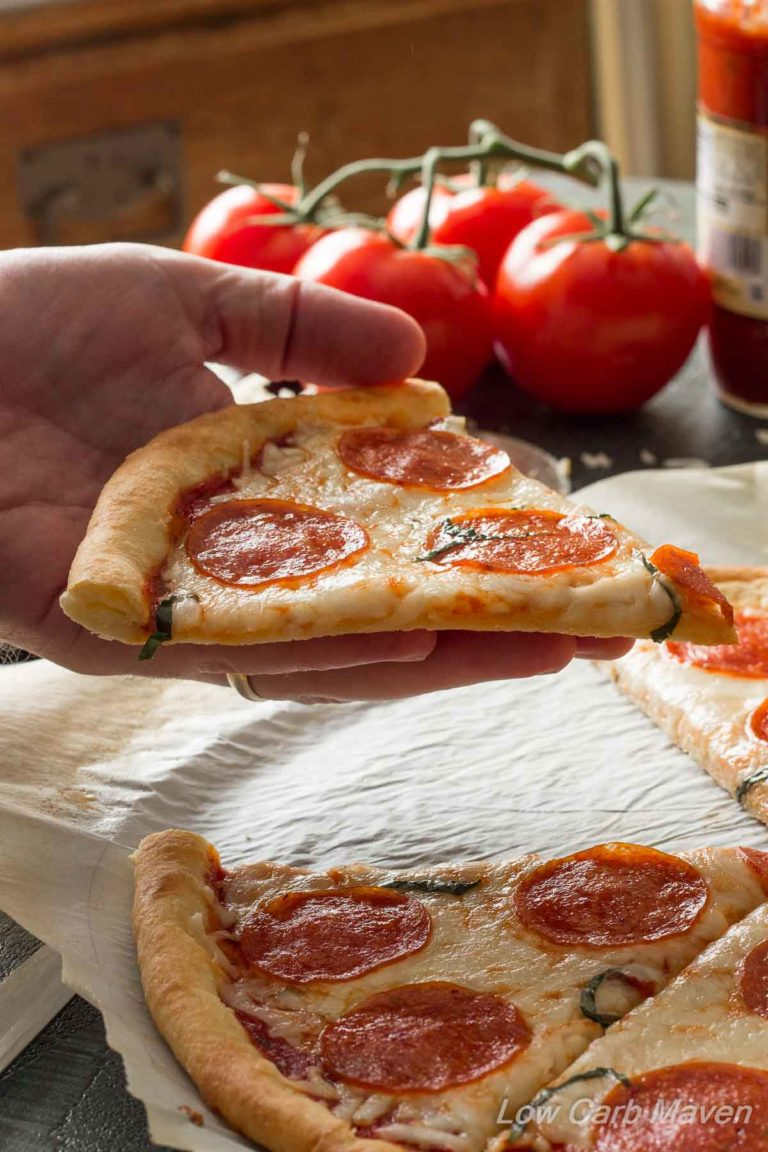 Sliced Low Carb Pepperoni Pizza with a hand held slice and tomatoes in the background.