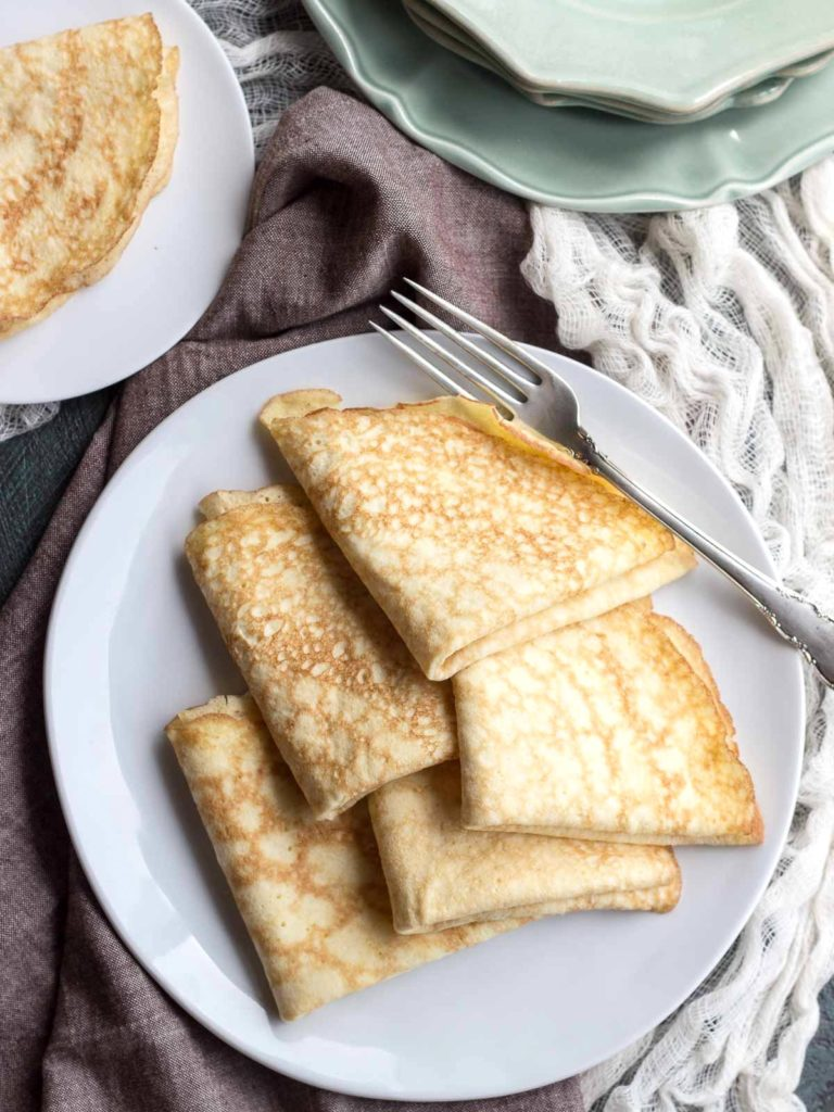 Folded low carb coconut crepes stacked on a plate with a fork. #crepes #lowcarb #keto #coconutflour #sugarfree #glutenfree