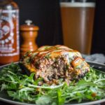 Portobello mushroom stuffed with ground beef, spinach, and cheese on an arugula salad with beer and siracha hot sauce in the background.