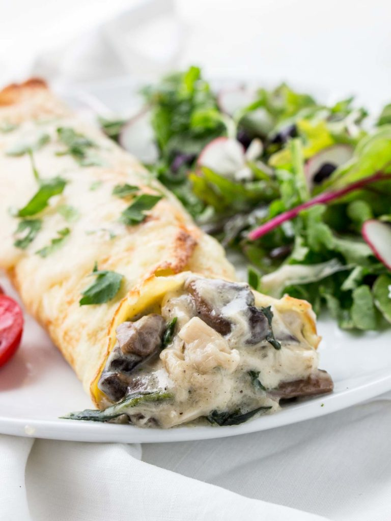 Chicken Florentine Crepes on plate with salad and tomatoes.