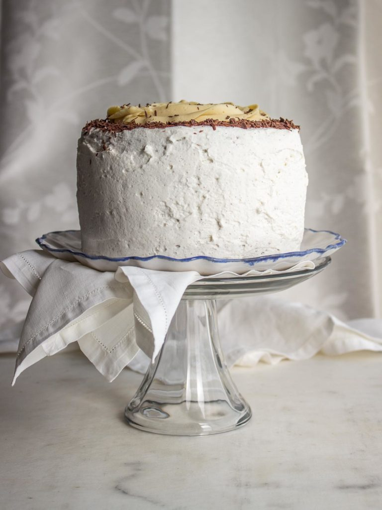 Chocolate cake with white frosting on a cake stand.