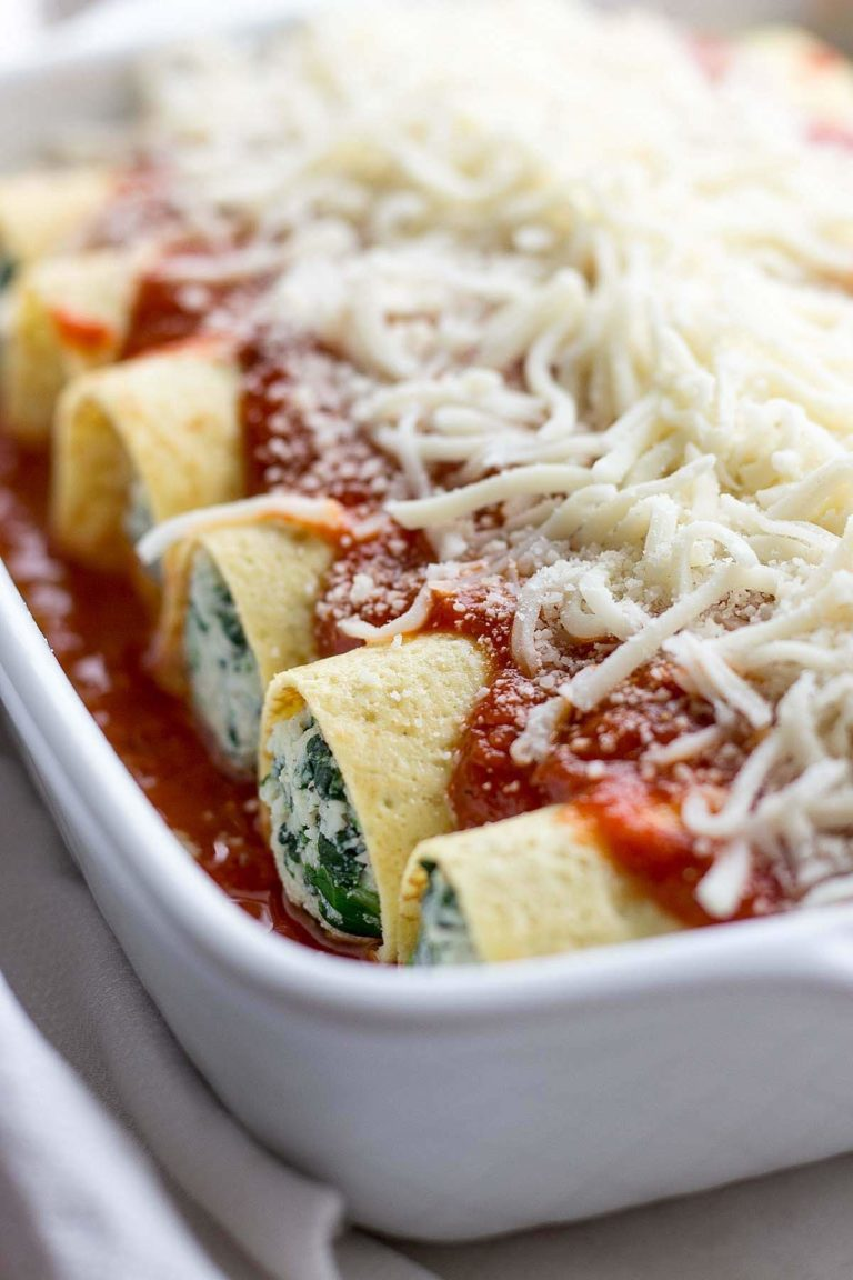 This delicious recipe for low carb spinach manicotti features crepes filled with spinach and ricotta cheese topped with marinara sauce and mozzarella cheese.