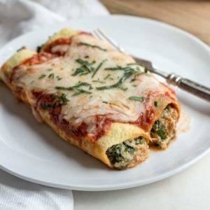 White plate with low carb spinach manicotti and fork.