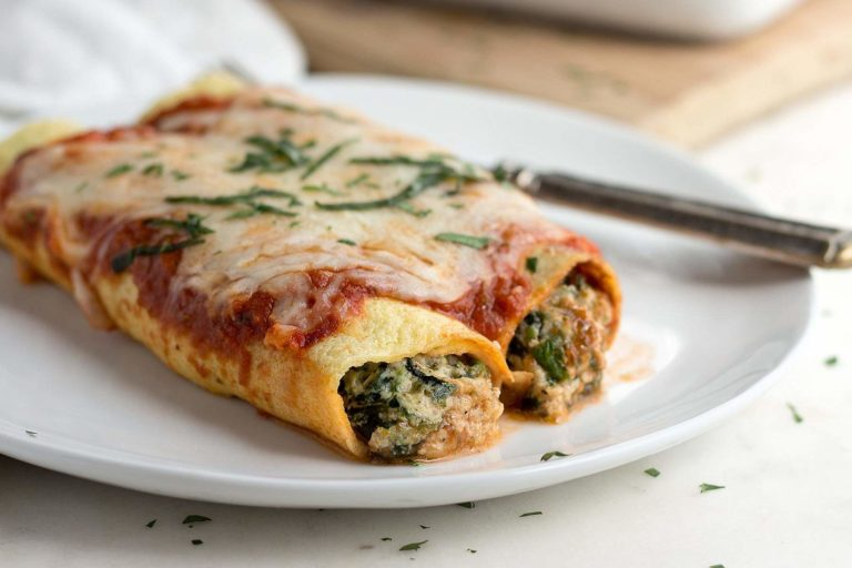 Low carb spinach manicotti on a white plate.