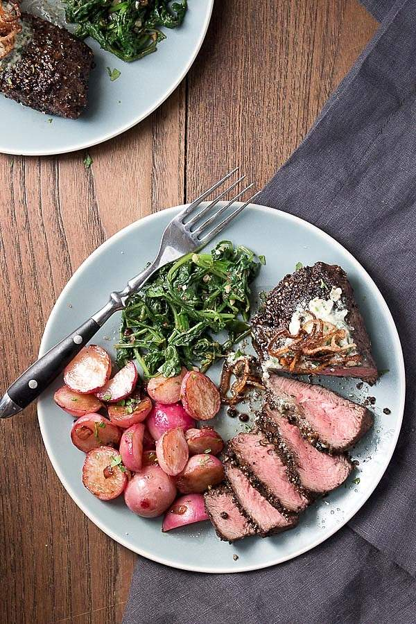 Sliced pan seared flat iron steak with a peppercorn crust and blue cheese butter on a light blue plate with pan fried radishes and sauteed radish greens.