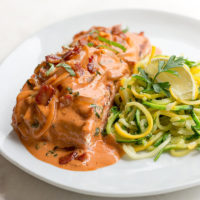 Cooked salmon filet sauced with creamy Tuscan sauce of tomato, bacon, basil, cream and vodka with spirilzed zucchini on the side.