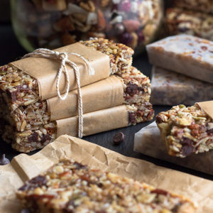 Nut and seed granola bars on wrinkled brown parchment, wrapped up in parchment, stacked, and tied with string, wrapped in waxed paper and a jar of nut and seed granola in the background.