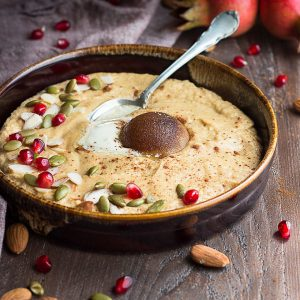 Pumpkin spice almond flour porridge with brown sugar, flaked almonds, green pumpkin seeds and red pomegranate seeds on top all in a dark brown drip glazed bowl on a brown wooden surface with nuts, seeds, and pomegranates around the bowl.