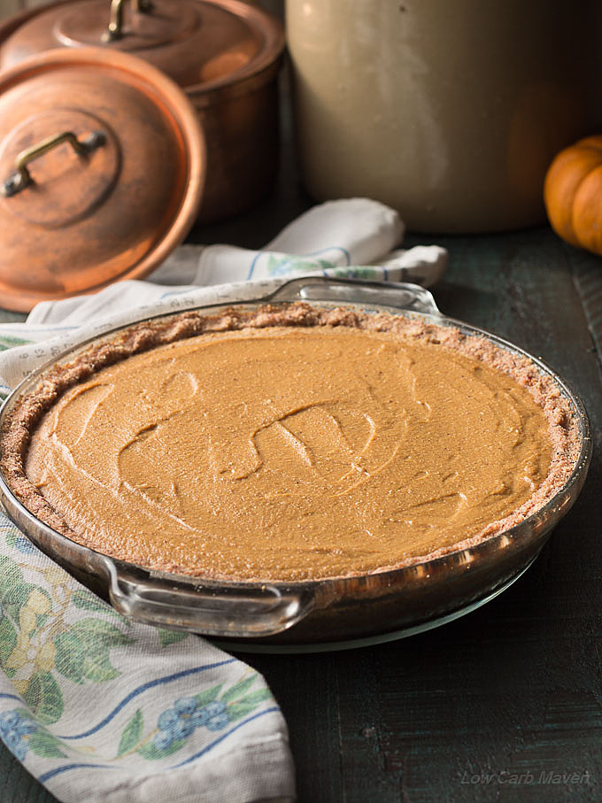 Whole sugar-free pumpkin pie with a nut crust in a glass pie plate with a floral napkin to the left and copper pots in the back ground.