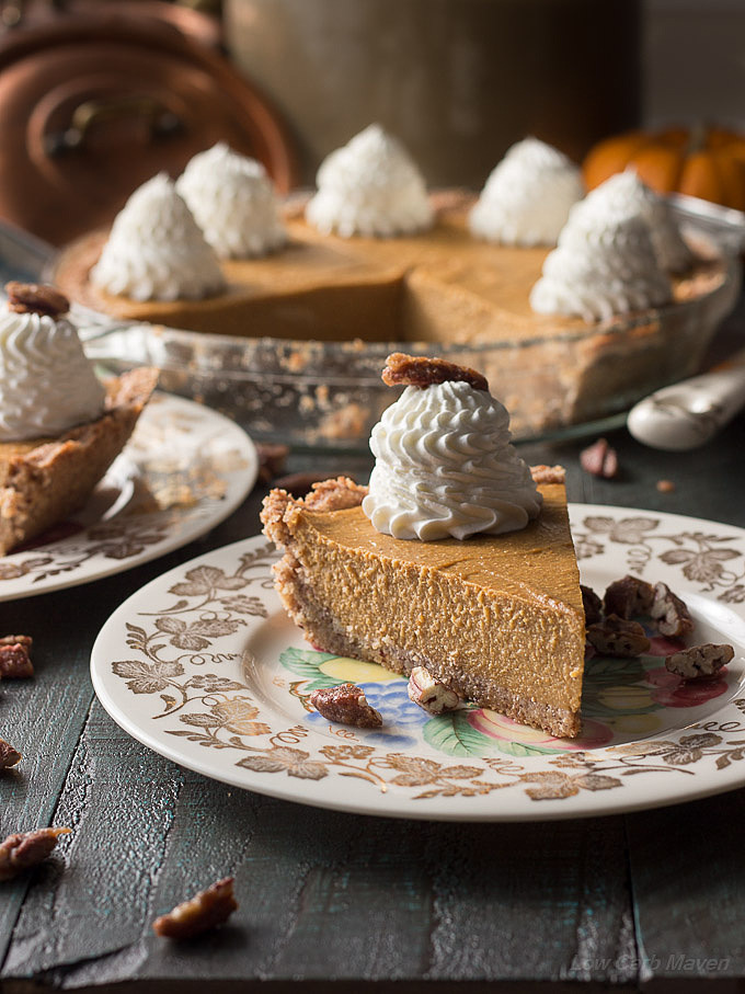 A slice of sugar-free pumpkin pie with a large ruffled dollop of whipped cream on a china plate decorated with gold grape leaves. A sliced pie is in the background decorated with mountains of piped ruffled whipped cream.