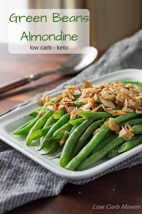 Green beans Almondine on white plate with sliced almonds on top.