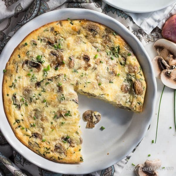 Top down view of a crustless mushroom quiche (with a slice missing at 5:00) in a white ruffled baking dish surrounded by a floral napkin and sliced mushrooms.
