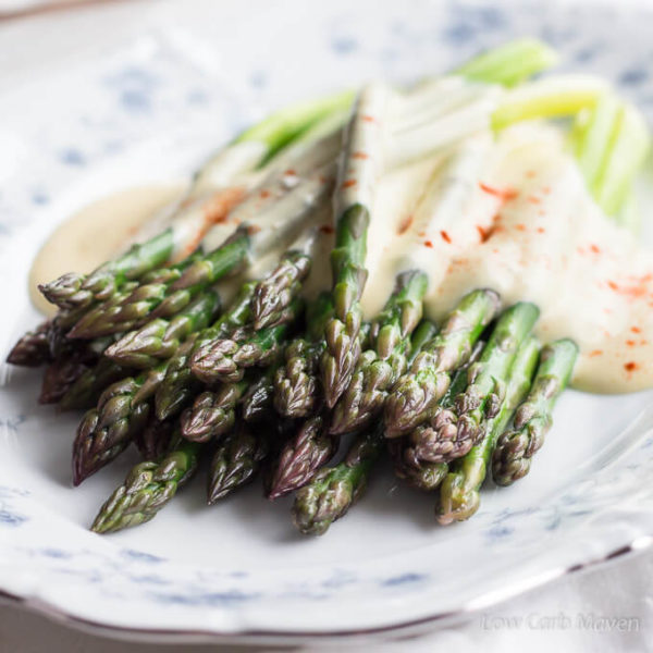 A view from the tip end of steamed asparagus (showing purple and green variations in color) with brown butter Hollandaise and paprika on an oval blue and white floral china plate with a silver edge.