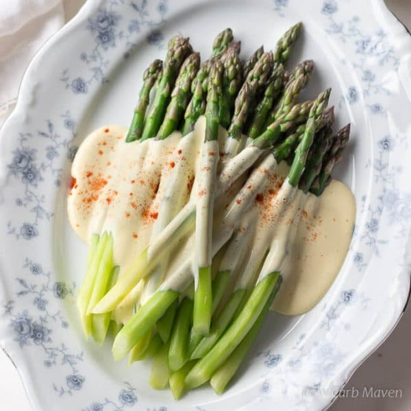 A top-down view of bright green steamed asparagus spears dressed with a rich yellow sauce of browned butter Hollandaise sprinkled with paprika arranged on a oval blue and white floral china plate.
