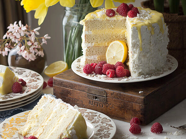 White layer cake filled with lemon curd, frosted with whipped cream and decorated with flaked coconut and raspberries sitting on a vintage china plate on an antique wodden box.