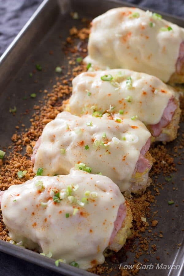 Four baked chicken breasts topped with low carb breading, slices of ham and melted Swiss cheese with sliced scallions on top in a small metal sheet pan with additional toasted crumbs in the bottom of the pan.