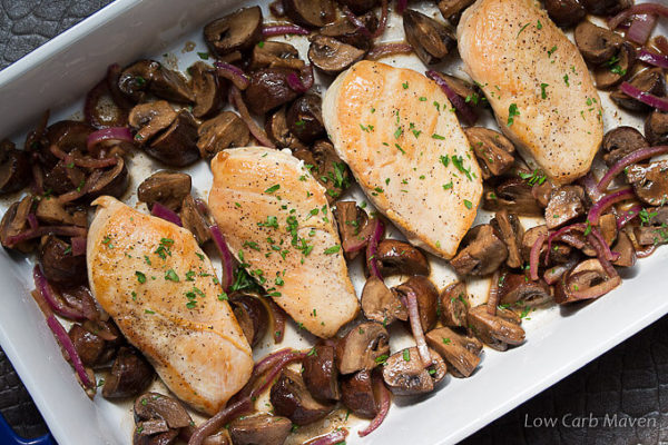 Chopped parsely spinkled over four browned chicken breasts with cooked mushrooms and purple onions in a white rectangular porcelain baking dish.