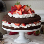 Low carb chocolate cake made with almond flour and filled with strawberries and whipped cream or whipped coconut cream. dairy free, keto, thm