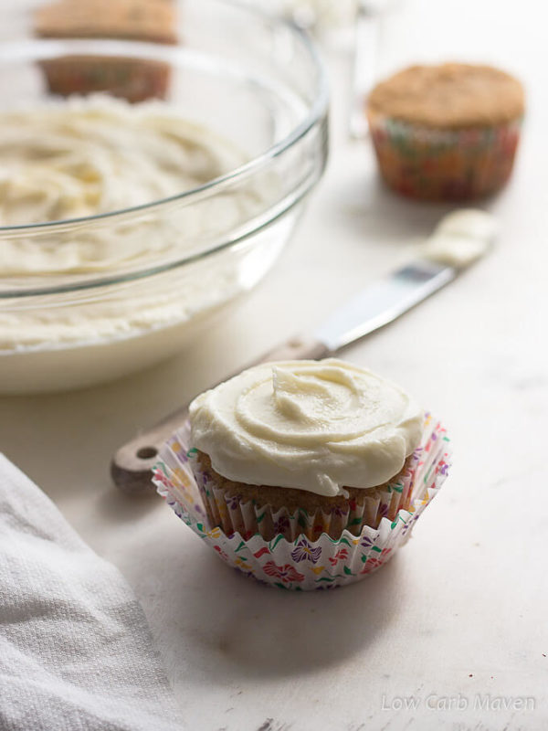 A cupcake in bright floral paper is topped with silky sugar free cream cheese frosting with a white towel to the left side, a small wooden handled stainless-steel spatula with frosting on it's tip is behind the cupcake as is a large clear glass bowl of cream cheese frosting and additional un-frosted cupcakes in the back ground.