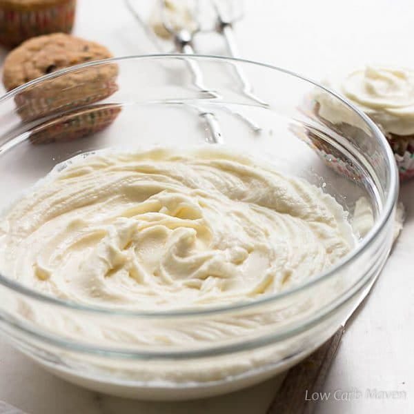 A large clear bowl of swirled sugar free cream cheese frosting with beaters placed behind and un-frosted cupcakes to the left of the beaters and a frosted cupcake to the right all on a white marble surface.
