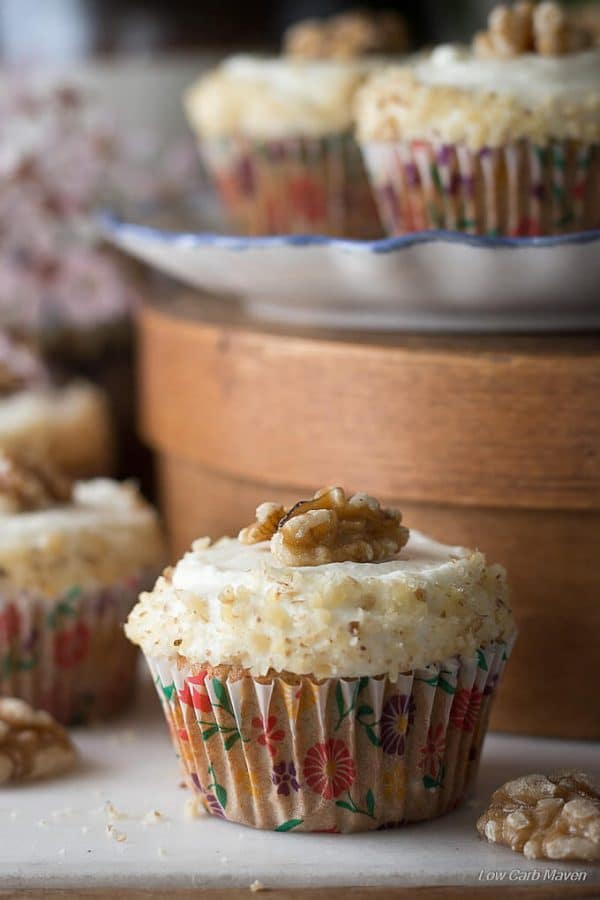Low carb sugar free carrot cake muffin with fluffy cream cheese frosting decorated with finely chopped walnuts around the side and a walnut half on top in a colorful floral fluted cupcake paper with more cupcakes to the side fading into the background and two cupcakes sitting on a blue and white ruffled plate on a brown round wooden cheese box behind.