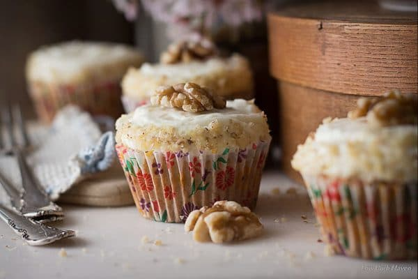 Close up of carrot cake cupcakes in colorful floral cupcake papers decorated with fluffy cream cheese frosting, finely chopped walnuts, and walnut halves with forks on a white cloth to the left and a brown wooden round box to the right.