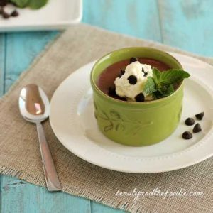 Chocolate mint pudding in a green ramekin with chocolate chips, whipped cream and a mint leaf.