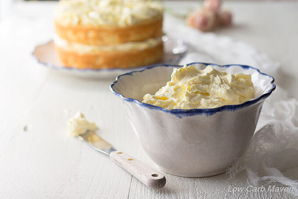 Low carb Sugar free French buttercream frosting in a white ruffled bowl with a blue edge between a small wooden handled spatula on the side with frosting on it's tip and a white piece of gauzy cheesecloth with a partially decorated cake in the background and pink roses.