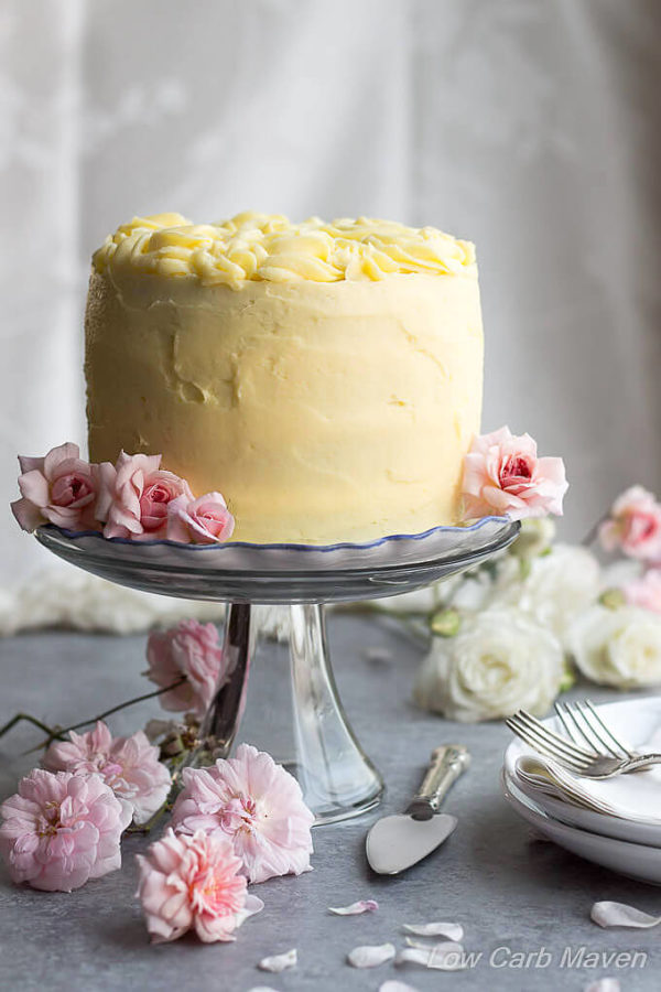 A layer cake decorated in yellow frosting with rosettes on top sitting on a clear pedestal with white and pink roses.