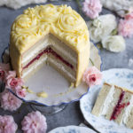Cut white layer cake on a pedestal decorated with yellow frosting and rosettes on a table decorated with white and pink roses and blue and white china dishes.