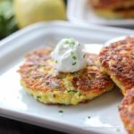Zucchini fritter with sour cream and chives on a white plate.