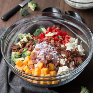 Ingredients for Amish broccoli cauliflower salad in a clear glass bowl: broccoli florets, cauliflower, red bell pepper, purple onion, cheddar cheese and bacon.
