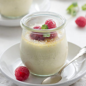 Vanilla bean creme brulee with raspberries in a glass jar on a while plate with a silver spoon.