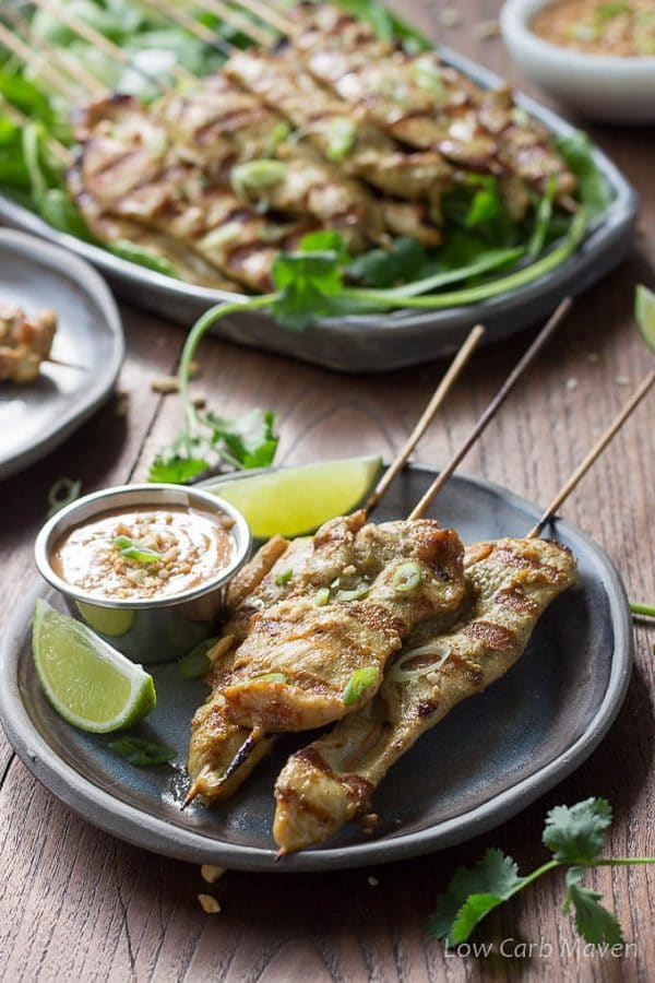 Thai chicken satay, marinated chicken threaded on bamboo skewers and grilled, on a gray plate served with peanut sauce and limes.