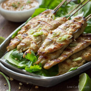 Grilled Thai chicken satay threaded on bamboo skewers on lettuce leaves on a gray plate served with peanut sauce and limes.