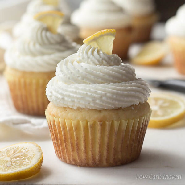 Sugar free lemon cupcakes frosted with mounds of whipped cream cheese frosting and topped with lemon slices.